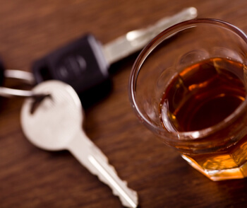 shot glass full of dark colored alcohol on top of a bar table along with a set of car keys. Drinking and driving series. Also driving under the influence of alcohol.